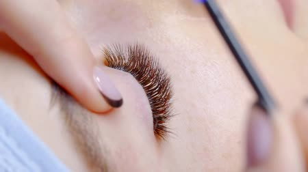 kiterjesztés : Cosmetologist finishing procedure on eyelashes, make up.