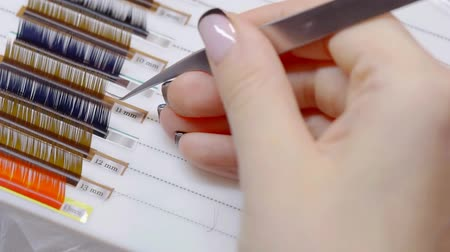 pinça : Woman picking colorful artificial eyelashes on extension procedure, beauty salon.