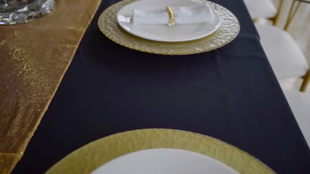 функция : top view on plates standing on blue tablecloth in restaurant in evening, fabric napkins are lying over