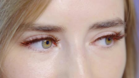 longer : close-up of beautiful green eyes of young woman, she is blinking and demonstrating her extended false lashes