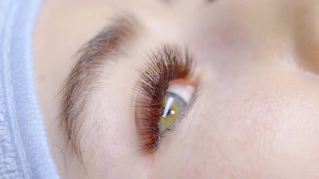 иностранец : close-up view of female eye with extended false lashes, she is lying in office after procedure