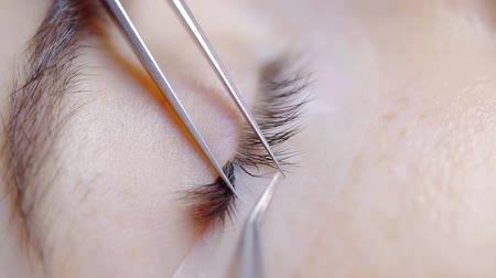 склеивание : beautician is correcting false lashes and separating filament on female eyelids, close-up in beauty salon