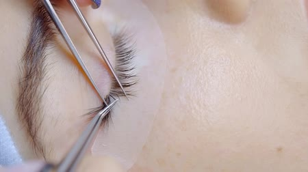 склеивание : master is performing procedure of lash extension on female eyelids in a beauty clinic Стоковые видеозаписи