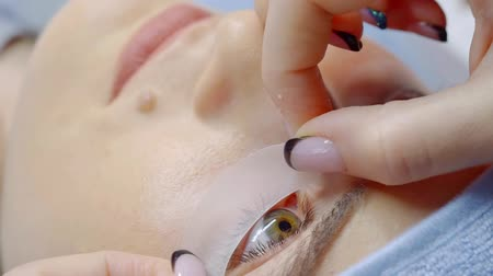 склеивание : cosmetologist is pasting protective patches under eyes before lamination of eyelashes in a salon Стоковые видеозаписи
