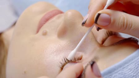 склеивание : lash maker master is cleansing eyelashes of woman by cotton stick before procedure of lash extension