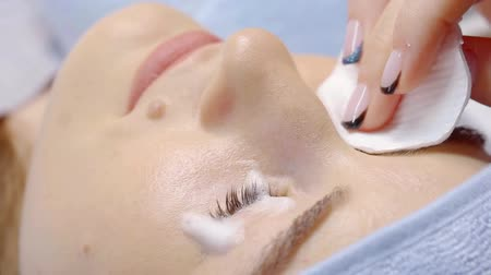 иностранец : cosmetologist is applying cleaning foam on lashes and eyelids of female patient, lying on a table