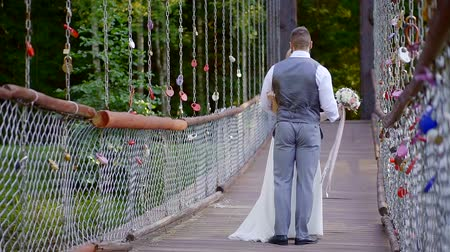 новобрачный : happy newlyweds are dancing on hanging bridge in summer day, romantic ritual Стоковые видеозаписи