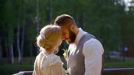 прижиматься : bearded groom is looking on his graceful blonde bride, leaning to her, loving pair is standing on a coast of lake Стоковые видеозаписи