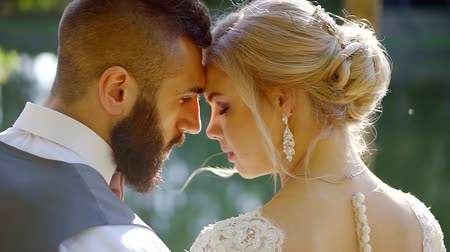 прижиматься : adult man and woman are wearing wedding dress and suit are hugging outdoors in summer sunny day
