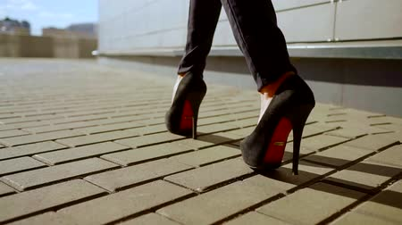 sassy : female feet booted fashionable high heels shoes are stepping on tiled surface outdoors in sunny day