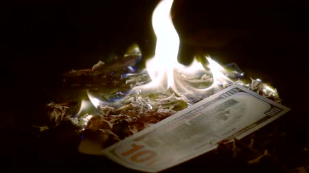 enflasyon : flaming dollars banknotes in dark room on a table, one hundred dollars is falling in fire Stok Video