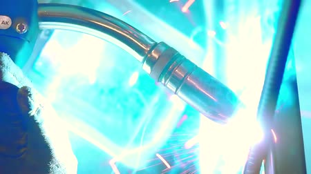 fire arms : close-up view of process of welding, bright blue light and sparkles are flying on sides