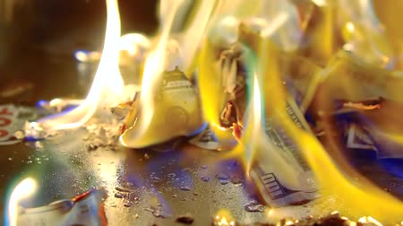 tutuşturmak : A pile of burining cash on the ground, bills in flame.