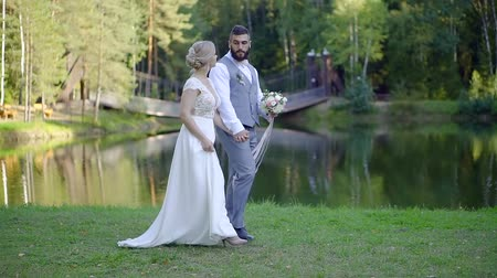 жених : Married couple walking in summer park on their wedding, brides coming to ceremony. Стоковые видеозаписи