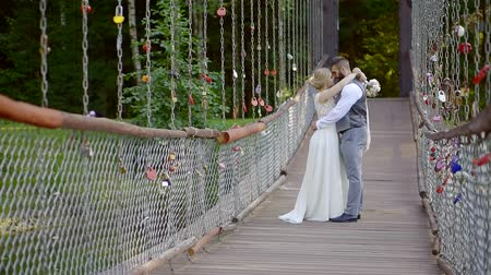 новобрачный : Beautiful couple of brides cuddling on bridge in nature, outdoor wedding in summertime.