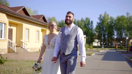 новобрачный : Couple of newlyweds happily walking outdoor in summer, happy marriage.
