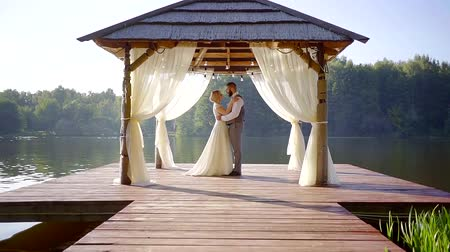 veranda : romantic pair of groom and bride in a veranda on a wooden pier of picturesque lake in summer day, approaching Dostupné videozáznamy