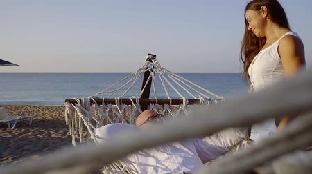 sessiz : Romantic moment on the beach, beautiful couple resting in hammack. Stok Video