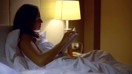 inteligentní : Woman reading book in bed light of a desk lamp.