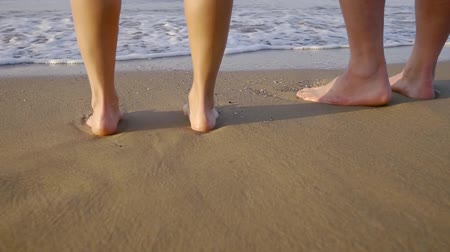 ślady stóp : Close-up shot of a couple standing barefoot on a beach in summer vacation at sea.