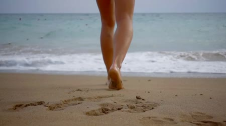 yalınayak : Woman walking into water leaving footprints on wet sand, beach vacation. Stok Video