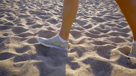 spor ayakkabısı : Close-up shot of a woman in white sneakers walking on beach, beautiful white sand.