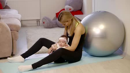 crouch : young athletic mom resting after a workout with her baby playing sitting on the gym Mat resting his back in fitball