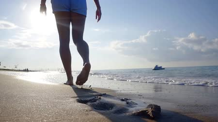 ślady stóp : Shot from behind of a female tourist walking on summer beach, footprints on sand.