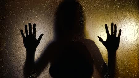 hallucination : scared woman is holding hands on transparent screen and moving back, silhouette