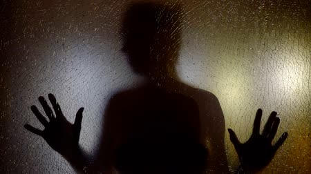 duchy : scary movie shot of woman is knocking y both hands with open palms in glass screen in darkness, silhouette view