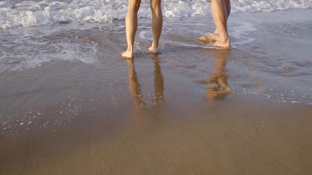 barefooted : legs of man and woman are walking on beach, waves of sea are washing them, close-up of feet in summer day