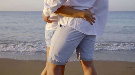 feliz : woman is stroking ass of her beloved man, close-up, couple is standing on sea beach in morning