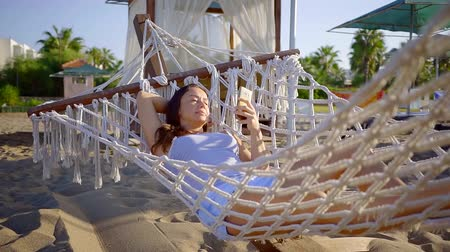 phone call screen : relaxed woman is resting in a wicker hammock in sand beach in summer morning, using smartphone