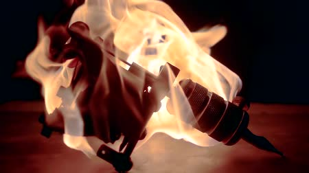 fireplace : burning tattoo machine are standing on a table in dark room, amazing dramatic shot Stock Footage