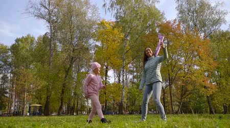 przedszkolak : joyful little girl and her mother are playing in sunny fall day in park throwing toy plane