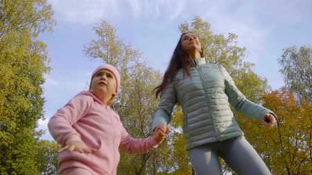 paper airplane : little girl and her mother are running in a park and holding hands, throwing small airplane