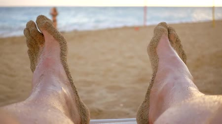 żart : male feet are covered wet sand, close-up, man is lying on a deckchair on a sea beach Wideo