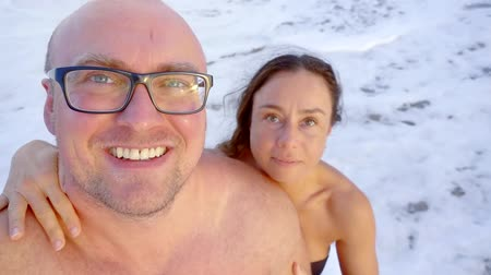 sharing : pretty brunette woman is hugging her lover on sea beach, man is taking selfie by camera