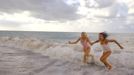 spaventato : funny scared women are fleeing from big waves on a sea beach, they are screaming and holding hands