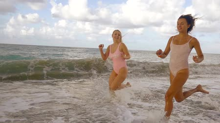 болваны : two pretty happy girls are running over water in a beach and jumping joyfully, water is splashing