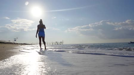 stroll : amazing slow motion shot of walking woman on beach with picturesque waves and clouds in sunny day