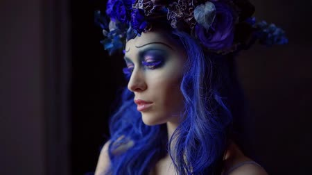 bizarre : Halloween face art. Portrait of beautiful woman with Halloween makeup corpse bride. Blue accents on hair and eyes, black background