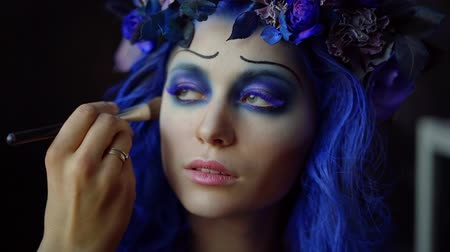 kanlı : Close-up portrait of a beautiful girl with fantastic blue makeup, long colored eyelashes. the hand of the make-up artist puts a tone on the cheek with a brush. Stok Video