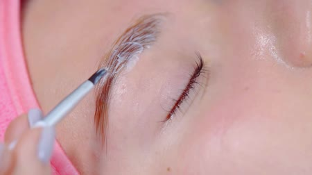 longer : aesthetician is covering female eyebrows by color dye, close-up of fingers and brush, client is opening eyes