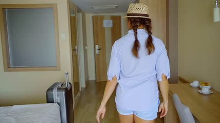 off : tourist girl is putting straw hat, looking at mirror in hotel room, taking suitcase and leaving chamber