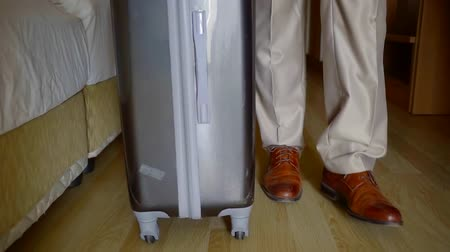 Войти : close-up view on expensive leather shoes of man and suitcase, he is walking in hotel room