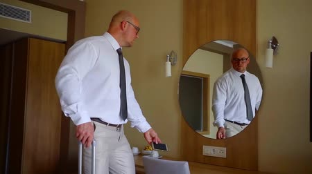 Войти : tall bald man is entering in light hotel room with suitcase, rolling it, typing on his smartphone