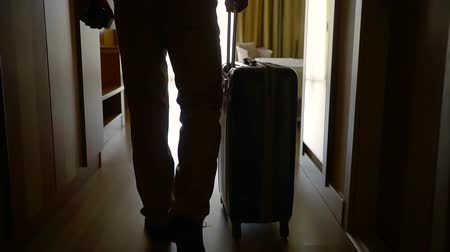 Войти : male guest of hotel is carrying his suitcase in room in daytime, walking over dark hallway Стоковые видеозаписи