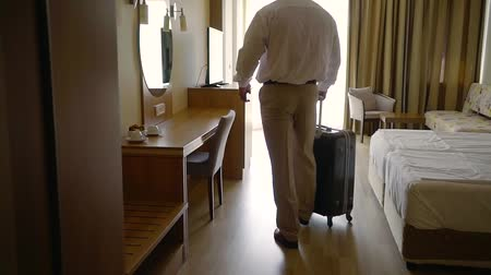 Войти : adult strong man is walking in new hotel room in daytime after checking, switching on lights