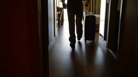 Войти : businessman is walking in hotel room, holding suitcase with wheels, back view Стоковые видеозаписи